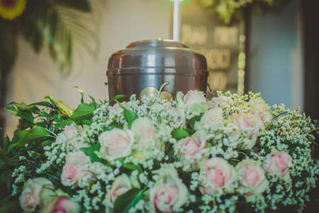 A metal urn with ashes of a dead person on a funeral with noone around on a memorial service. Sad grieving moment at the end of a life. Last farewell to a person in an urn.