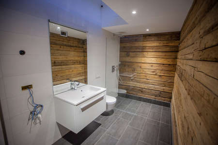 A modern bathroom with wooden walls and grey tiles on the floor. White tiles on the floor, bit mirror and a walk in shower with glass wall. Fancy looking home bathroom. Stock fotó