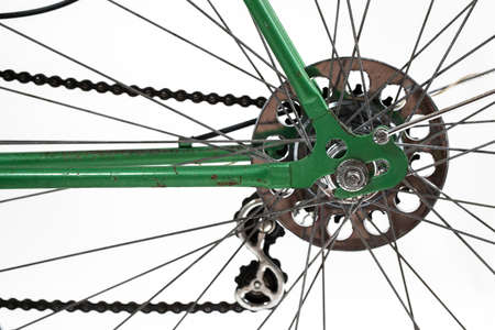 An old retro looking green vintage city bicycle for women, isolated o white background. Closeup or detail of rear hub, deraileur, casette and chain. Axle with nut is visible.