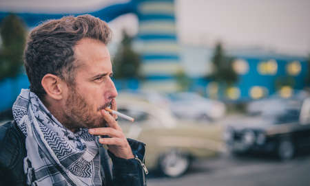 Hipster looking young caucasian man lighting up a cigarette and smoking. Man enjoying a cigarette. Vintage cars in the background. Retro man in vintage ambient smoking a cigarette