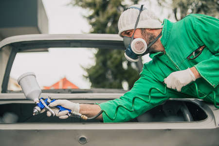 Caucasian man is spraying color with a compressed air paint gun on the vintage car as a restoration project. Man wearing protective equipment such as mask and gloves, professional automotive painter.
