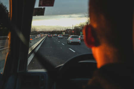 Man driving a car on a motorway with some traffic, looking over the shoulder. Romantic sunset evening setting.