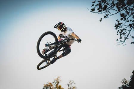 Frontal shot of a mountain biker jumping over a dirt jump in a bike park performing a tail whip .