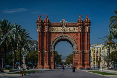 Arc de triomphe or arch of triumph in Barcelona, Spain in a clear sunny day with only a few tourists lingering by. Frontal shot of Arc de Triomphe in Barcelona. Banque d'images