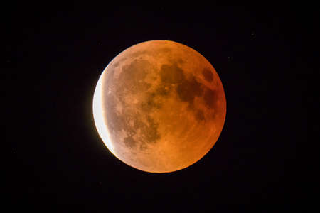 Red or blood moon, full moon eclipse in 2018. Astronomical picture of red moon in an eclipse phase with sun just starting to shine on the left. Stock Photo