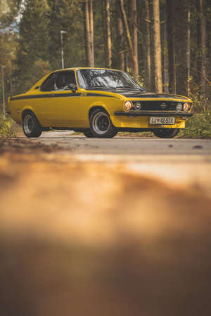 BRNIK, SLOVENIA, 28.10.2019: Vintage Opel Manta A GT/E car in yellow color parked on the street in an autumn forest.