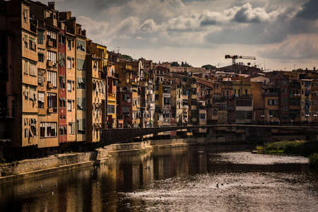 Dark looking panorama of Girona from the river, looking away from Girona cathedral of Saint Mary and red Eiffel bridge. Greenery on the water is seen. Foto de archivo