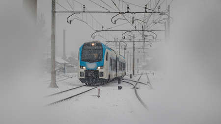 Modern commuter passenger train is rushing through the dense snowfall or snow which is hindering drivers sight. Urban city setting