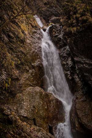 Fast flowing water over small rapids and waterfalls in Vintgar gorge, close to Borovnica, slovenia, on a dull winter day.