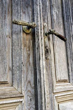 Old decorated door handles on weathered doors  photo