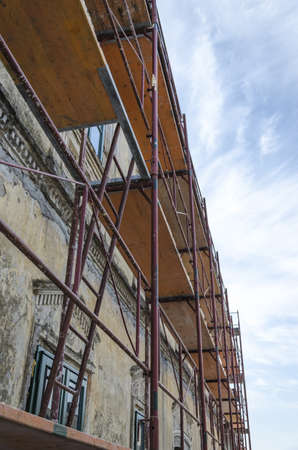 Scaffold surrounding old house during renovation works  photo