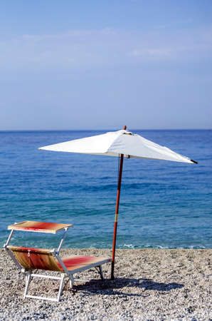 recliner: Recliner and umbrella on a pebble beach. Stock Photo