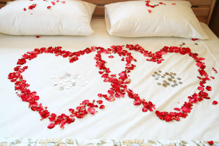 Red rose hearts on white bed. Stock Photo - 8816780