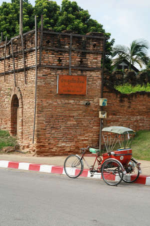 a tricycle and antique Chiang Mai city wall, Thailand
