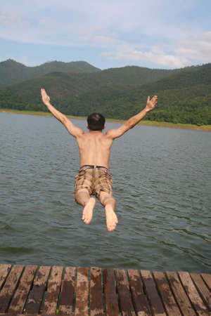 a asia man jump to lake water with mountain view background  photo