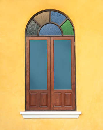 wood window with colorful glass on yellow wall  photo
