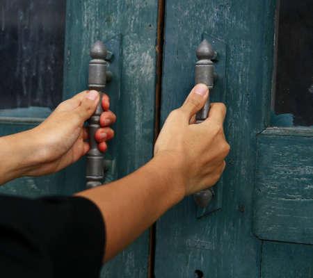 tocar la puerta: asimiento de la mano el mango de la puerta de madera Foto de archivo