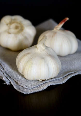 Garlic on fabric , black table photo