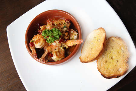 sizzling: close up Spanish tapas dish, sizzling prawns with chili and garlic Stock Photo