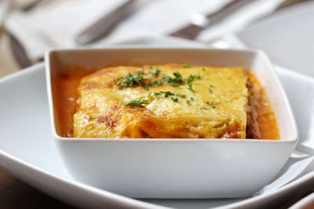 close up italian lasagna on a square plate photo