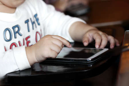 kid hand play smart phone on table photo