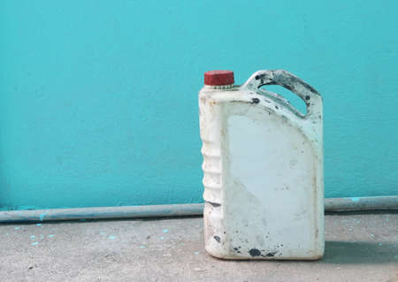 benzine: old benzine gallon on blue wall background Stock Photo