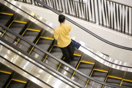 mopped: maid is cleaning escalator Stock Photo