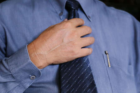 self conscious: Asian businessman use hand touch necktie