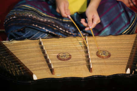 fingering: women hand play dulcimer Stock Photo