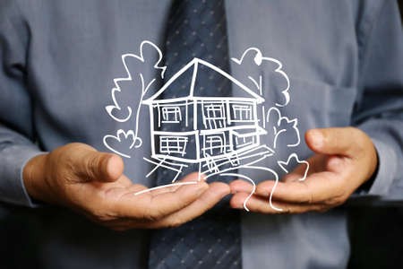 businessman use two hand hold house graphic