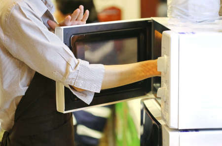 arm pick up food inside microwave oven, office kitchen Imagens