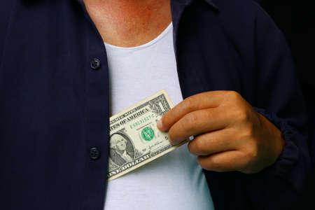 putting money in pocket: Corruption. Man putting money in suit jacket pocket