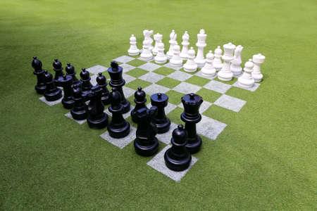 chess: Tablero de ajedrez y piezas de ajedrez sobre la hierba en el jardín