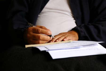 write letter: man write pen on document paper Stock Photo