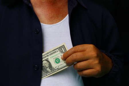 layoffs: Corruption. Man putting money in suit jacket pocket