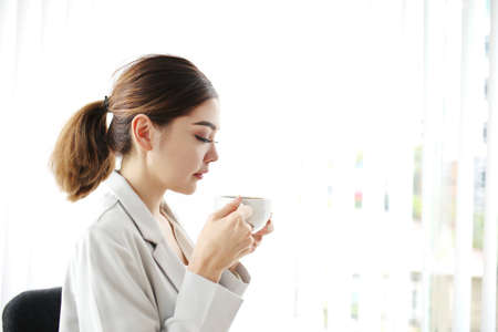 Young pretty woman sitting at opened window looking outside enjoys of rest. charming businesswoman with suit hand hold hot coffee cup drink in morning. Good life feeling roasted bean aroma Stock Photo