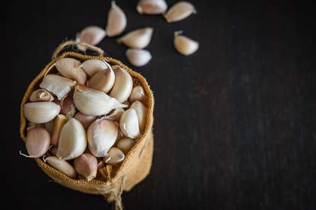 Fresh garlic in sack on wood table
