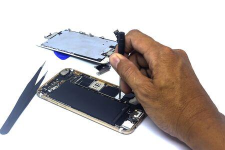 L'uomo a mano ripara lo smartphone con gli strumenti, isola, i danni allo smartphone devono essere riparati