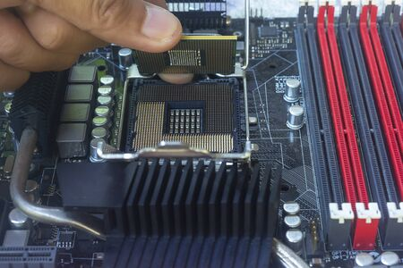 Gros plan sur la main du technicien mettant le processeur sur le socket de la carte mère de l'ordinateur