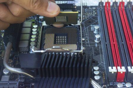 Nahaufnahme der Hand des Technikers, der die CPU auf den Sockel des Computer-Motherboards setzt