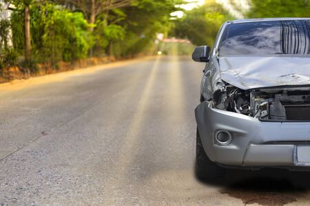 Front of light gray color car with pick up have big damaged and broken by accident on road in morning time can not drive any more park for wait insurance officer. With copy space for text or design