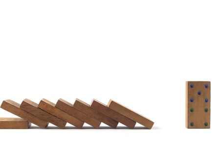 Social distancing concept wood domino toys on white background, . Domino effect. 8 dominos is falling and next one domino can stand. Фото со стока