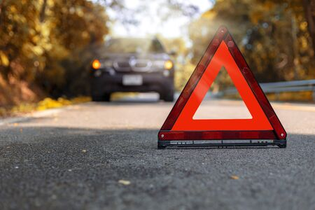 Red triangle, red emergency stop sign, red emergency symbol and black car stop and park on road.