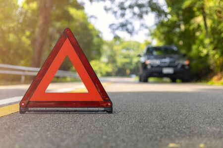 Red triangle, red emergency stop sign, red emergency symbol and black car stop and park on road. Archivio Fotografico