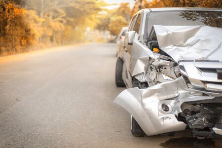 Autumn road front  light gray color car  pick up have big damaged and broken  accident on road in morning time can not drive any more park for wait insurance officer.