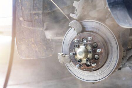 Mechanic use air gun clean disc break take dust removes before change break pat.