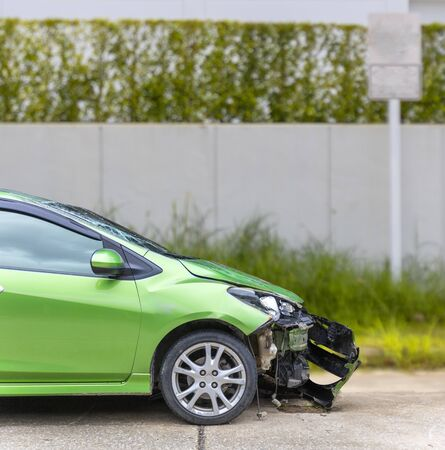 Front of green color car damaged and broken by accident on road parking can not dirve any more Фото со стока