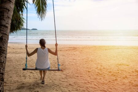 woman traveler sitting on the swing relex on the beach. women tourist enjoy with view of the sea on holiday time. Asia Thailand. With copy space for text or design