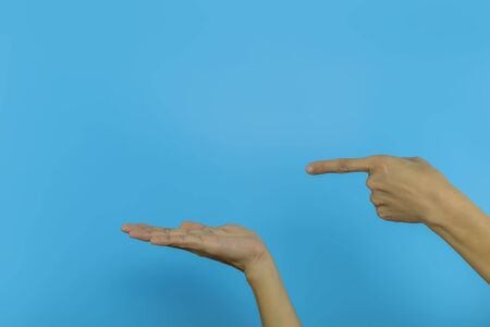 Women's hand Two hands One hand pointing the other hand Open hands on blue background with copy space. Human hand with copy space. for product or advertising . 免版税图像
