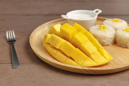 Fresh yellow mango peel and Sliced cubes with sticky rice ,coconut milk on wood plate . Tropical fruit. Thai dessert. Dessert fruit. Banco de Imagens
